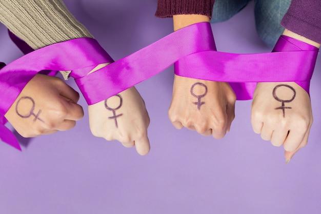 Primer plano de las manos de las mujeres con el símbolo del feminismo