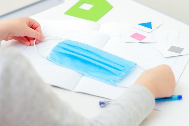 Primer plano de las manos del niño sosteniendo una máscara médica sobre el cuaderno durante el estudio en casa. concepto de escuela en cuarentena.
