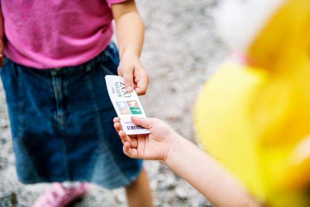 Primer plano de manos de niños dando boletos de zoo a otros