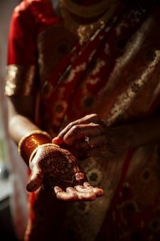 Primer plano de las manos de la novia hindú cubiertas con tatuajes de henna