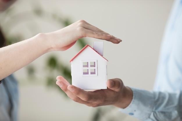 Primer plano de manos protegiendo modelo de casa pequeña