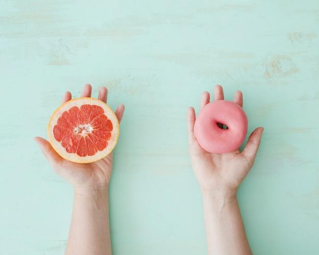 Primer plano de manos con rodaja de pomelo y donut rosa sobre el fondo con textura