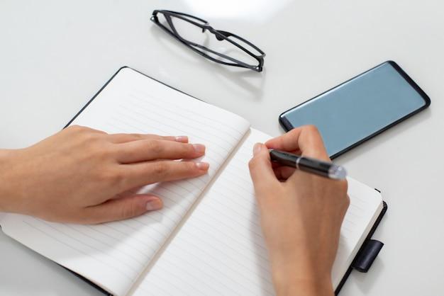 Primer plano de las manos de la secretaria anotando cita en el cuaderno