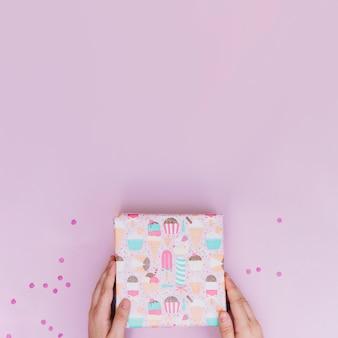 Primer plano de un manos sosteniendo la caja de regalo envuelto con confeti sobre fondo rosa
