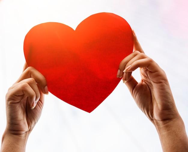 Primer plano de manos sosteniendo corazón de papel