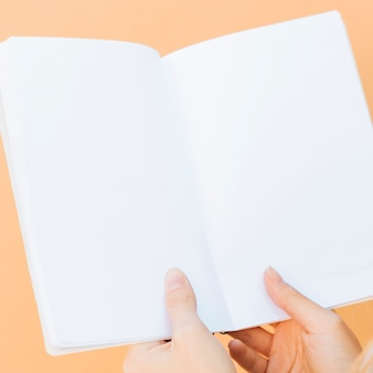 Primer plano de manos sosteniendo un libro blanco en blanco sobre fondo coloreado