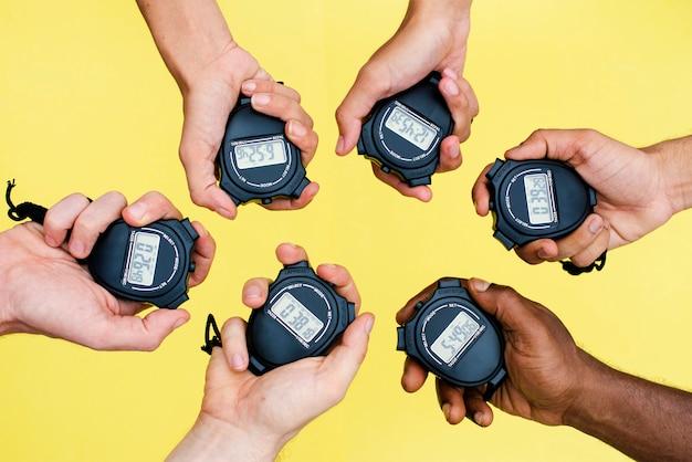 Primer plano de manos sosteniendo relojes de parada con fondo amarillo