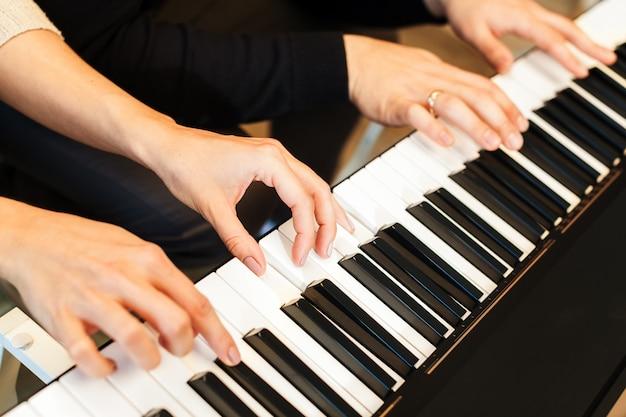 Primer plano de las manos tocando el piano. concepto de música y hobby.