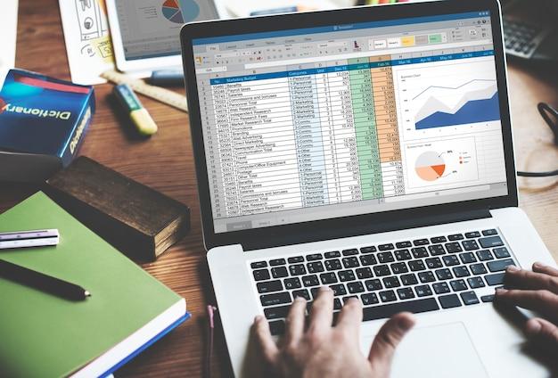 Primer plano de las manos usando la computadora portátil con pantalla que muestra datos de análisis
