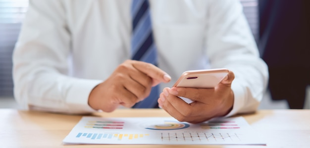 Primer plano de las manos usando el teléfono inteligente en la mesa de madera y escribiendo mensajes para asignar trabajos a los empleados.