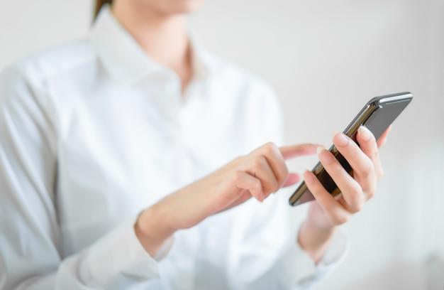 Primer plano de las manos usando el teléfono inteligente en la mesa de madera y escribiendo mensajes a sus amigos.