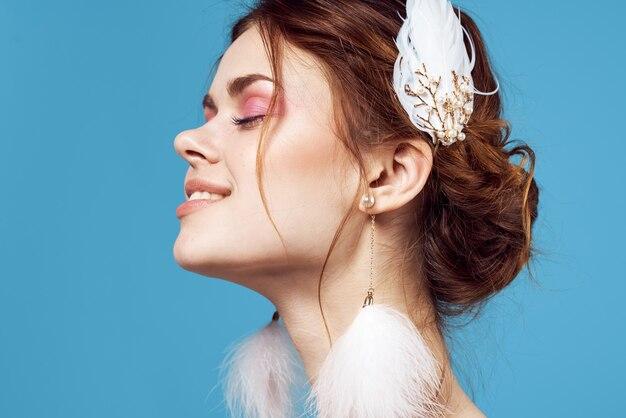 Primer plano de maquillaje brillante de mujer bonita hombros desnudos mullidos pendientes. foto de alta calidad