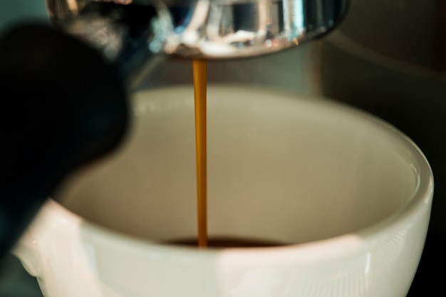 Primer plano de la máquina de café que hace la bebida del café express