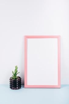 Primer plano de un marco de fotos vacío con una pequeña planta en maceta en el escritorio azul