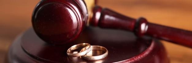 Primer plano de un martillo de juez y anillos de boda