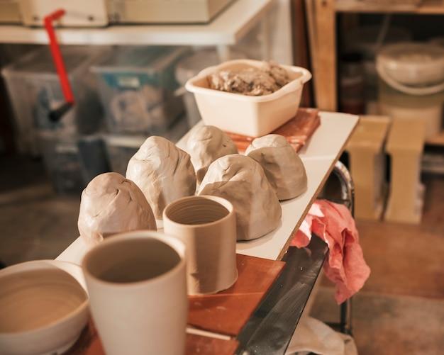 Primer plano de masa amasada; florero de cerámica en la mesa