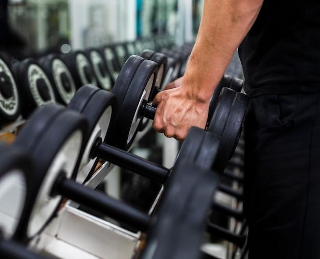 Primer plano masculino en el gimnasio eligiendo pesas
