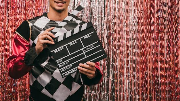 Primer plano masculino con pizarra de película en la fiesta de carnaval