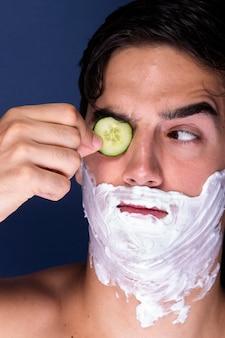 Primer plano masculino con productos para el cuidado de la piel