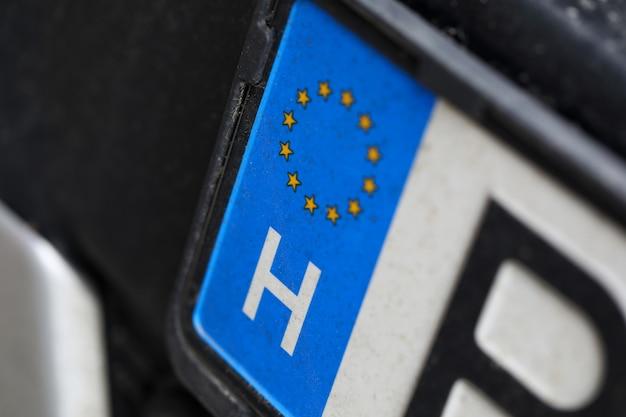 Primer plano de la matrícula europea del coche. automóvil de la ue. tiro macro del número de registro de la unión europea. pequeñas estrellas colocadas en círculo. concepto de vehículo y transporte.