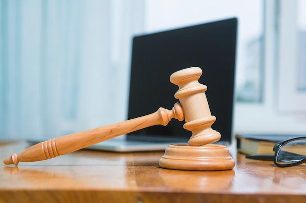 Primer plano de un mazo de madera en el escritorio en la sala del tribunal