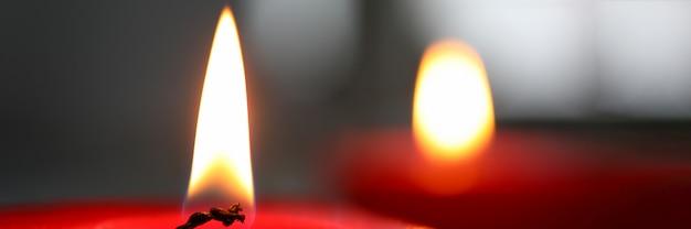 Primer plano de mecha vela encendida sobre la pared oscura