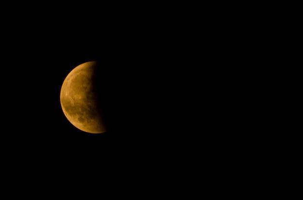 Primer plano de una media luna contra un cielo oscuro