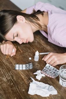 Primer plano de medicamentos con una mujer enferma apoyada en un escritorio de madera