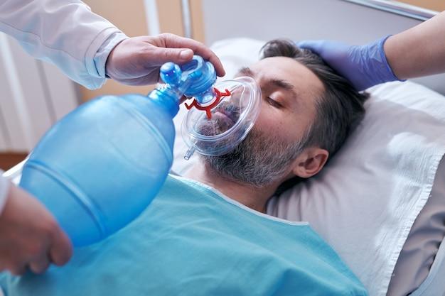 Primer plano de médico irreconocible colocando máscara de válvula de bolsa en la cara del paciente inconsciente