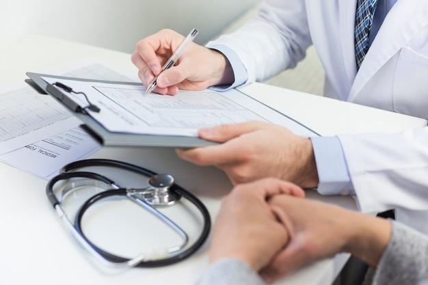 Primer plano de un médico llenando el formulario médico con el paciente