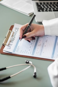 Primer plano de médico llenando formulario de seguro de vida