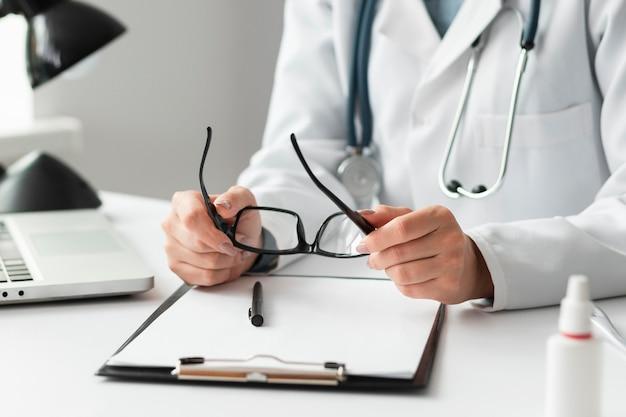 Primer plano médico sosteniendo anteojos