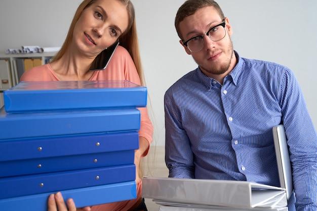 Primer plano medio de dos colegas que tienen una gran carga de trabajo cargada con múltiples carpetas de documentos