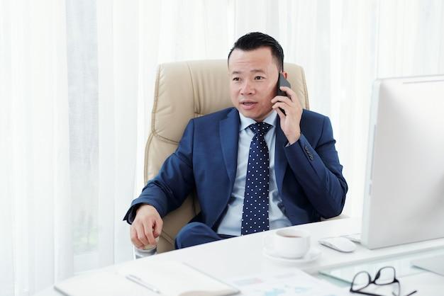 Primer plano medio de empresario asiático haciendo una llamada telefónica sentado en su escritorio de oficina