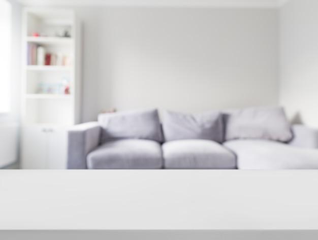 Primer plano de una mesa blanca frente a un sofá defocused