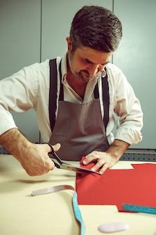 Primer plano de la mesa de sastres con manos masculinas trazando patrón de fabricación de tela para ropa en el estudio de taller tradicional. el hombre de profesión femenina. concepto de igualdad de género
