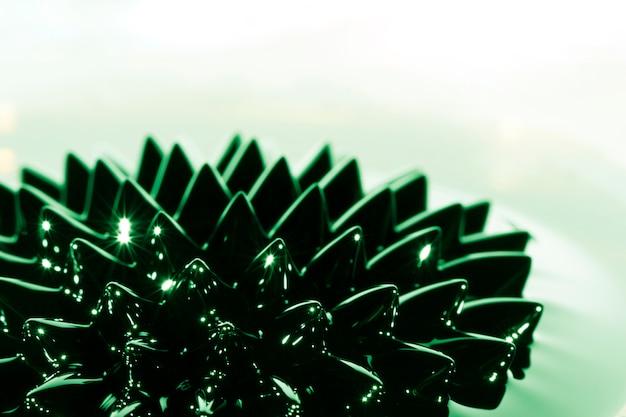 Primer plano de metal ferromagnético con sustancia verde