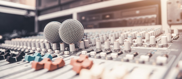 Primer plano del micrófono se coloca en el mezclador de audio profesional en el estudio.