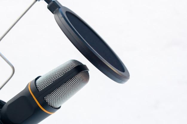 Primer plano de un micrófono negro y gris capturado sobre un fondo blanco.
