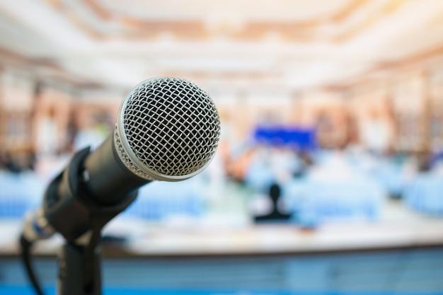 Primer plano de micrófonos en abstracto borroso de discurso en sala de reuniones