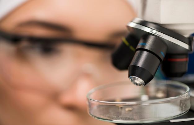 Primer plano del microscopio en el laboratorio con mujer científico