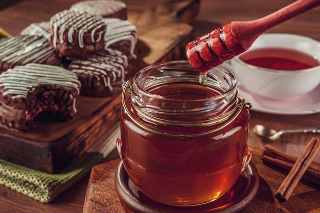 Primer plano de miel de abeja y galletas de miel brasileñas cubiertas de chocolate - pao de mel