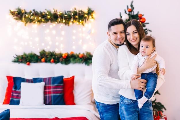 Primer plano de la mirada de la familia a la cámara en el fondo de la cama y el árbol de navidad.