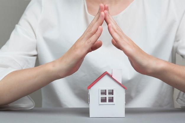Primer plano del modelo de casa de protección de la mano de la mujer en superficie gris