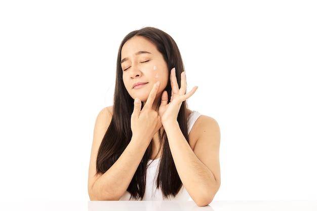 Un primer plano de una modelo con una crema hidratante en las mejillas. una mujer se aplica una crema humectante en la cara. una hermosa niña tiene una bonita piel facial. concepto de cuidado de la piel.