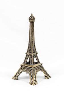 Primer plano de un modelo en miniatura de bronce de la torre eiffel aislado