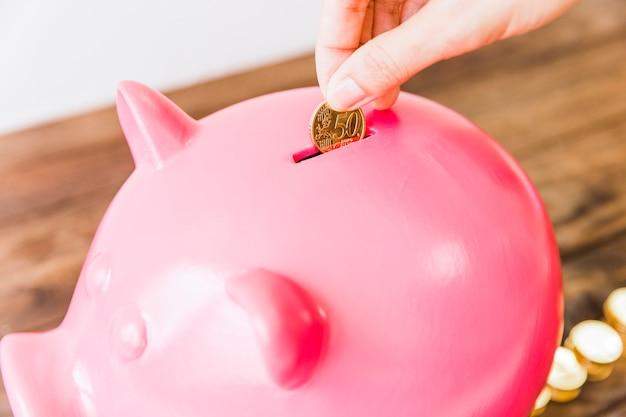 Primer plano de la moneda de ahorro de una mano de una persona en piggybank rosa
