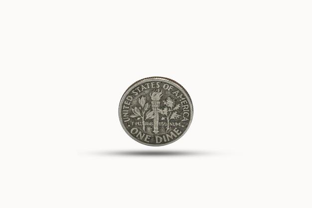 Primer plano de una moneda de diez centavos con sombra sobre fondo blanco.