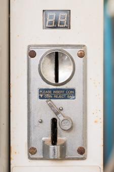 Primer plano de una moneda metálica de una ranura de monedas de una máquina que funciona con monedas con ranuras de entrada y salida