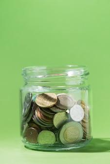 Primer plano de monedas dentro de un recipiente de vidrio sobre fondo verde